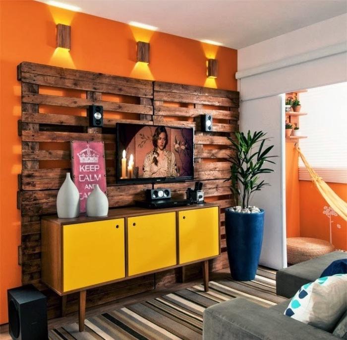 Стена из деревянных поддонов как основной акцент гостиной комнаты - это оригинальный вариант оформления интерьера и на первый взгляд может показаться, что телевизору совсем не место возле этой стены.