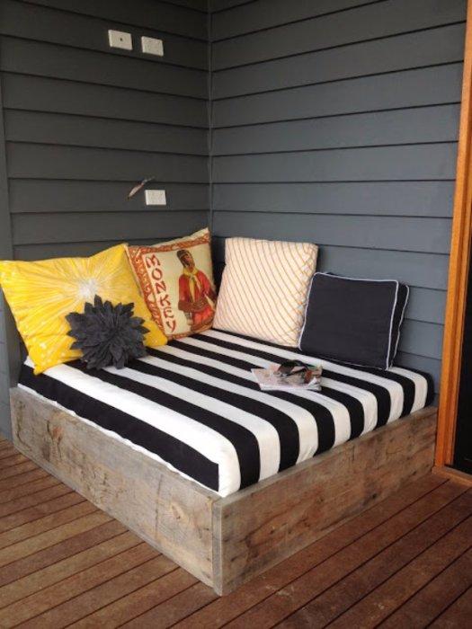 Удобный и стильный диванчик на крыльце с деревянным основанием, который позволит отдохнуть на свежем воздухе.