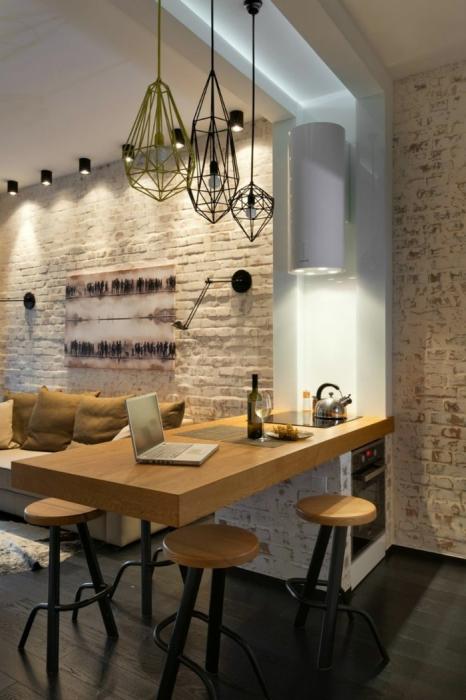 Необычная кухня с современной встроенной техникой, небольшим диванчиком и большой обеденной зоной в светлом тоне.