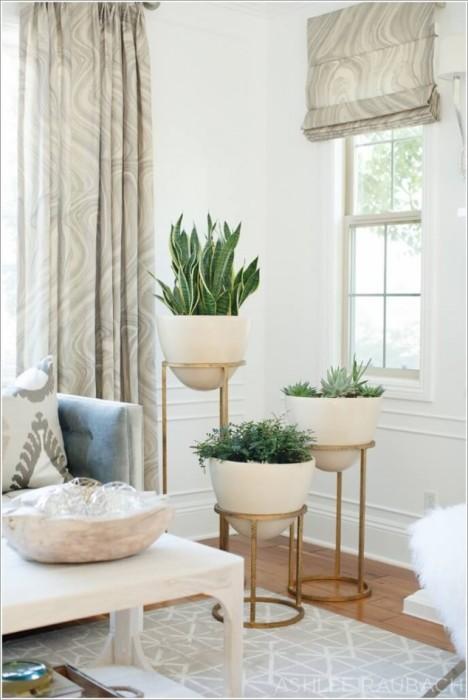 Кованые металлические подставки для кашпо, которые будут отлично смотреться в светлом интерьере гостиной комнаты.