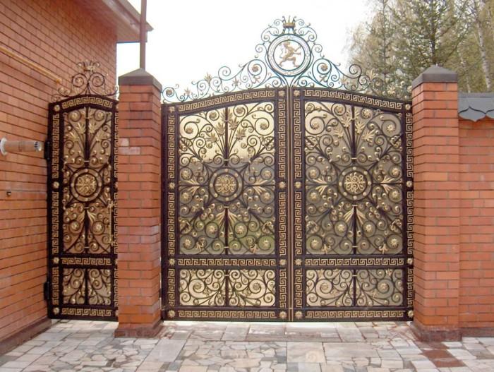 Необычные металлические ворота с кованными элементами с позолотой.