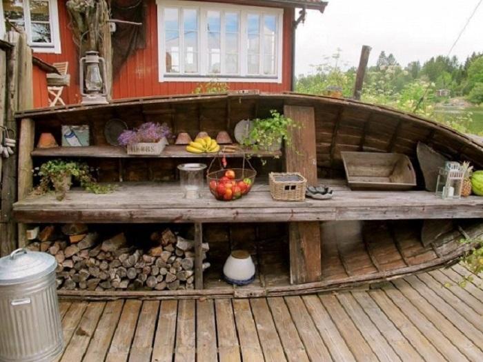 Старая деревянная лодка может стать незаменимой вещью на территории садового участка.