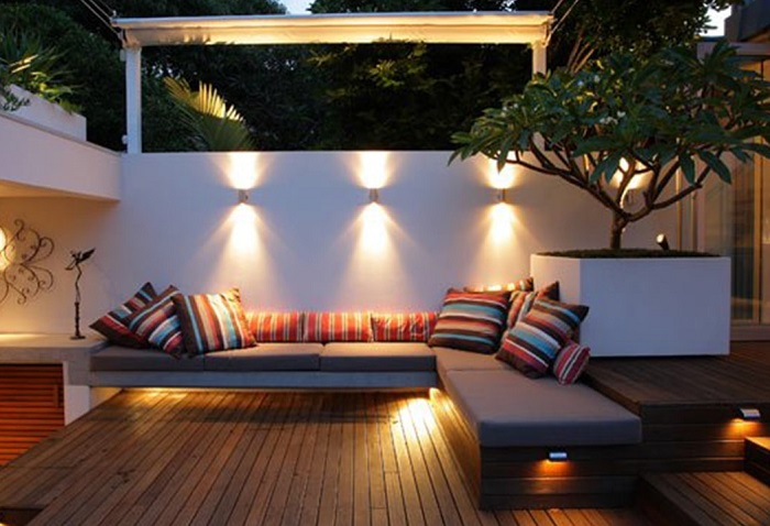 Літній патіо на дачній ділянці в стилі мінімалізму з кутовим м'яким диваном і незвичайним штучним деревом.