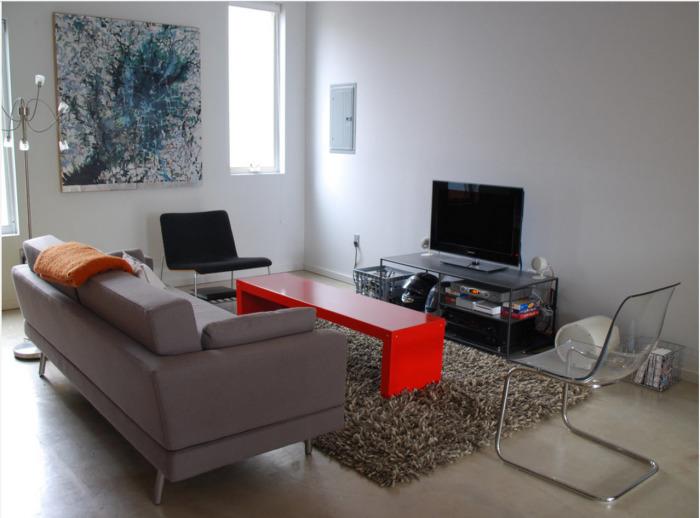 Современная гостиная комната в минималистском стиле с простым акцентным журнальным столиком красного оттенка.