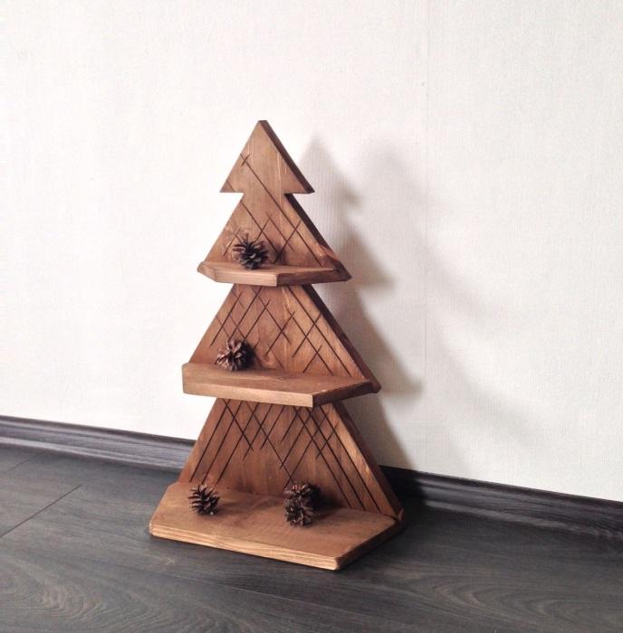 Небольшой деревянный стеллаж в форме ёлки с тремя полками, на которых можно расставить красивые новогодние фигурки или повесить гирлянду из огоньков.