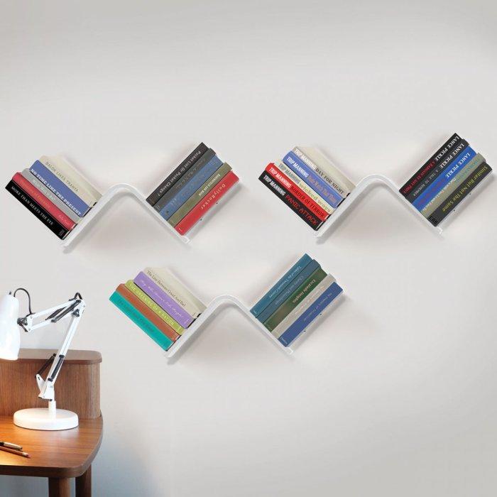 Небольшие настенные полочки для книг клиновидной формы.