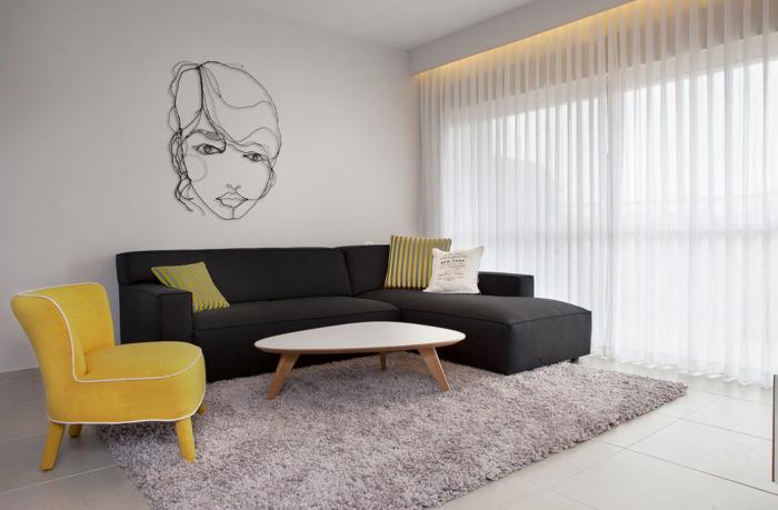 Большой угловой диван ненавязчивой тёмной расцветки, небольшой деревянный журнальный столик и жёлтое акцентное кресло в интерьере гостиной комнаты.