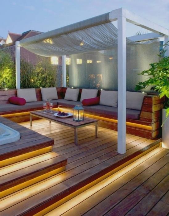 Нетривиальный дизайн веранды с хорошо подобранным освещением на территории загородного участка.