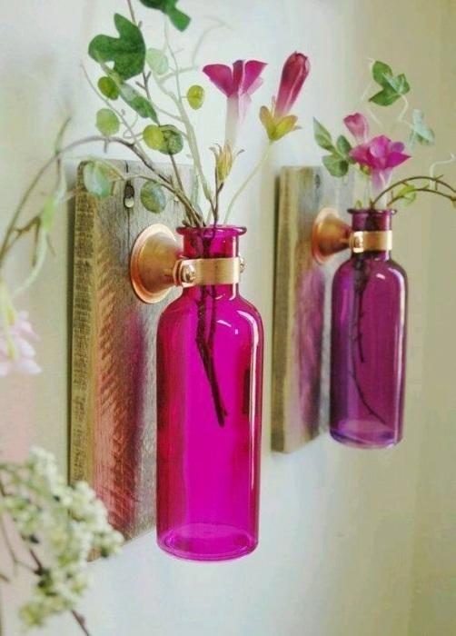 Настенные вазы из стеклянных бутылок розового цвета, спроектированные специально для искусственных растений.