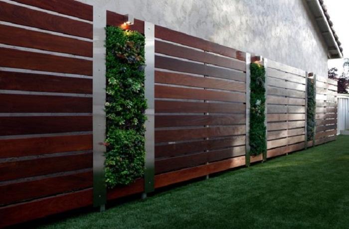 Декоративный деревянный забор из дорогой породы древесины выполняет не только роль ограждения и дизайнерского элемента, но и станет идеальным основанием для вертикального мини-сада.