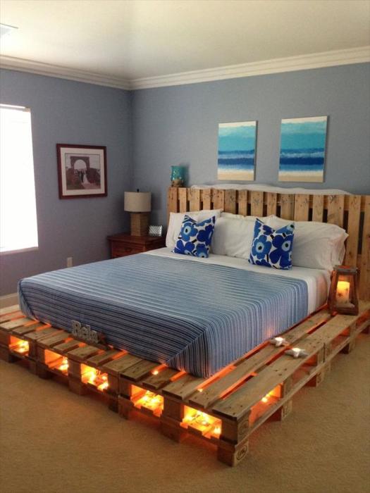 Необычный каркас кровати, выполненный из множества деревянных поддонов в несколько рядов.