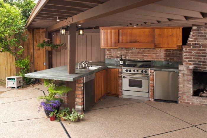 Гармоничное сочетание природных и искусственных материалов в интерьере летней кухни.