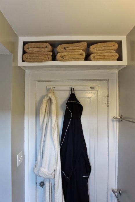 Если оборудовать открытую полку над дверью в ванной комнате, то без труда там можно расположить банные принадлежности.