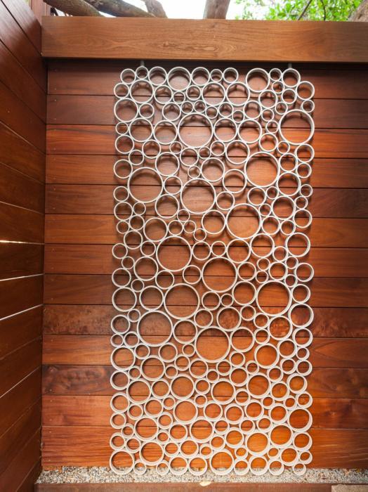 Деревянный забор, украшенный обрезанными поливинилхлоридными трубами разного диаметра.