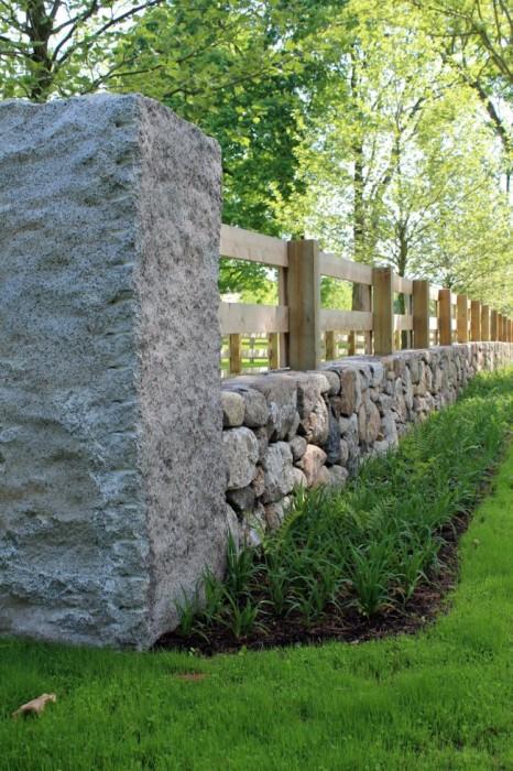 Комбинированный забор, в котором отлично сочетается дерево и камень может стать своеобразной визитной карточкой загородного участка.