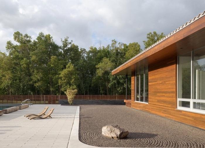 Необработанный камень на территории садового участка в минималистском стиле.