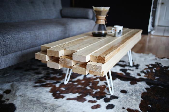 Кофейный столик из простых деревянных брусков и металлических ножек в гостиной комнате.