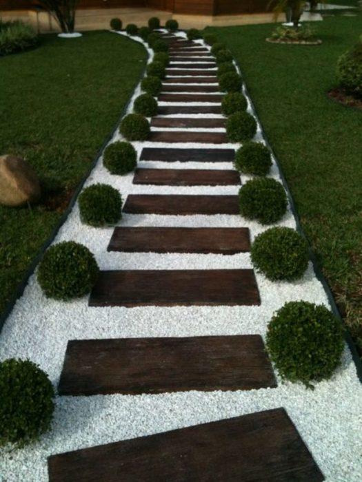 Садовая дорожка из деревянных досок на фоне белой гальки.