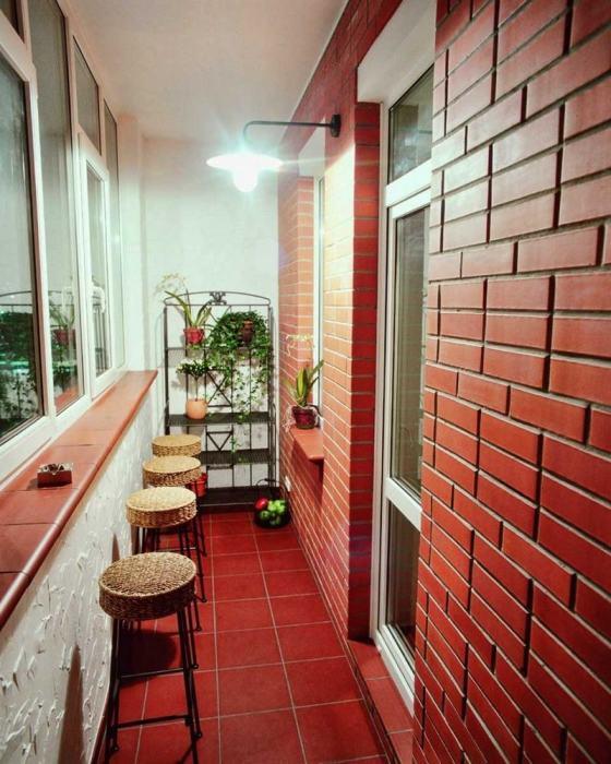 Отделка балкона красным кирпичом.