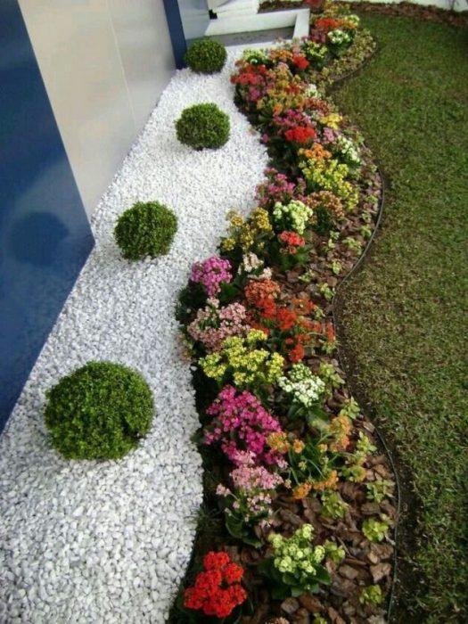 Аккуратно ухоженная декоративная клумба с однолетними растениями, белой галькой и четкими границами.