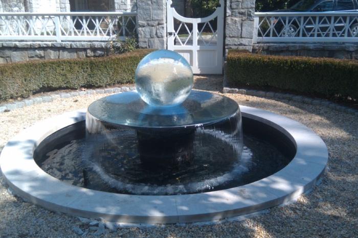 Современный дизайн фонтана со стеклянной сферой в ландшафтном дизайне.