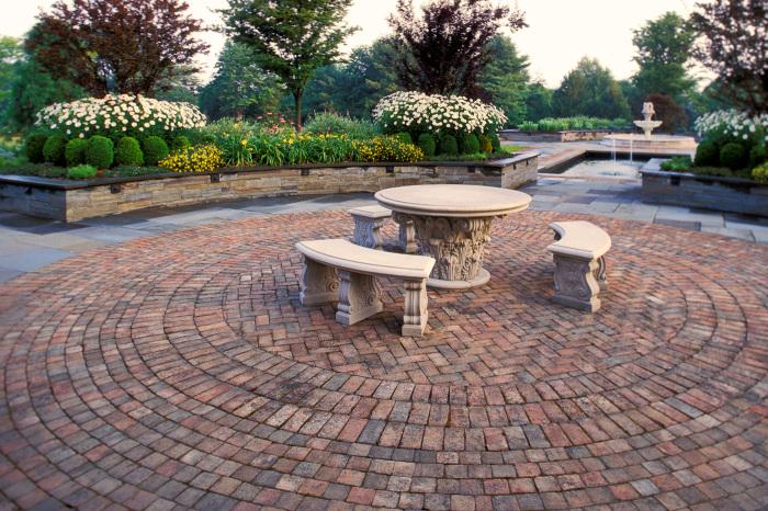 Каменные дорожки и мебель в древнегреческом стиле могут стать основным украшением садового участка.