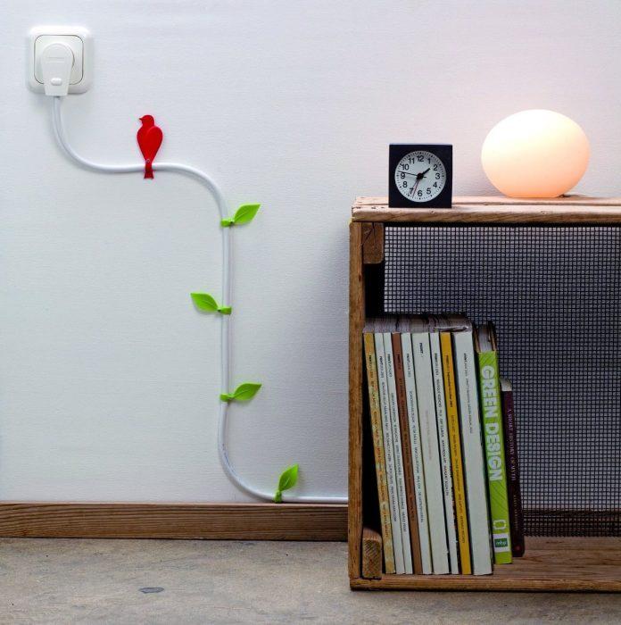 Шнур электропитания, украшенный зелеными листьями, отлично разрядит строгую обстановку в интерьере.