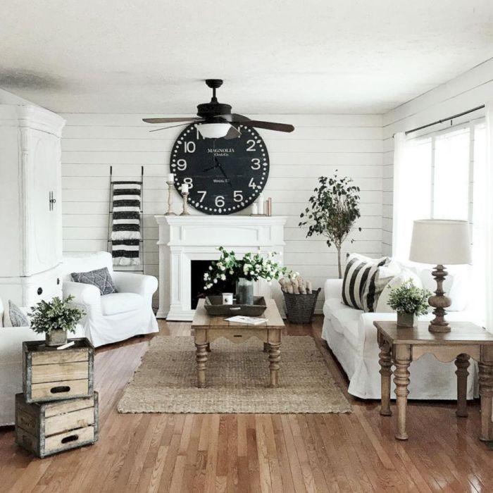 Светлая гостиная комната с множеством деревянных элементов, и с большими контрастными чёрными часами.