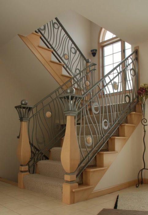 Классическая трендовая лестница с металлическими перилами и ступеньками из натуральной древесины.