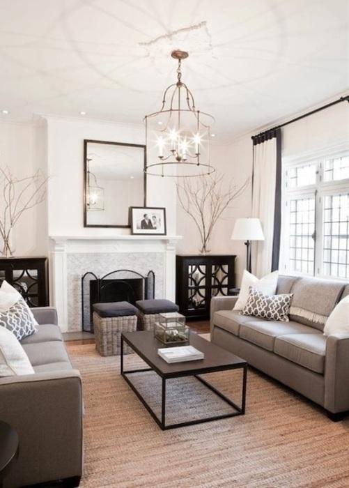 Гостиная комната в светлых тонах с шикарной мягкой мебелью, журнальным столиком и классическим камином.
