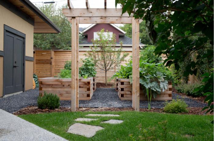Небольшой садовый участок с высокими деревянными клумбами и минимальной растительностью.