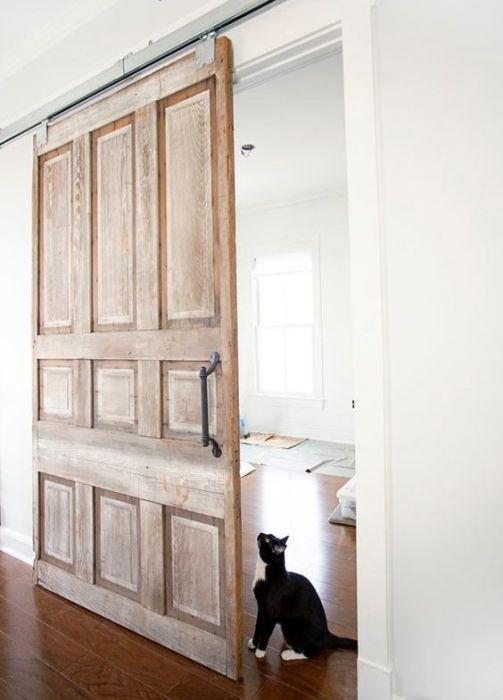 Раздвижные межкомнатные двери из дерева в классическом светлом интерьере.