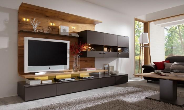 Модульная стенка, в которой сочетается пластик и дерево, впишется в любой интерьер гостиной комнаты.