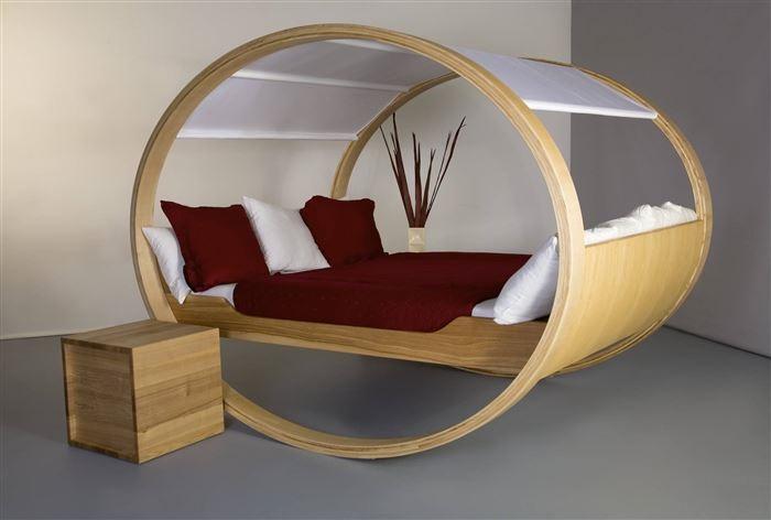 Невесомая овальная дизайнерская кровать с обилием деревянных материалов в минималистском стиле - отличный пример сочетания традиционных жизненных представлений и необычной мебельной концепции.