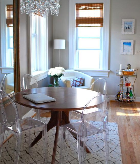 Гостиная комната с классическим круглым деревянным столиком из лакированного ясеня и прозрачными стульями из АБС-пластика.