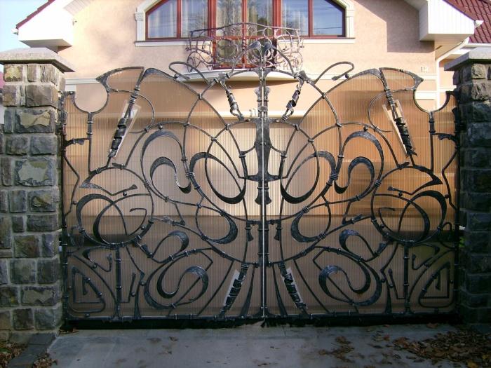 Оригинальные кованные ворота станут настоящим украшением для загородного участка.