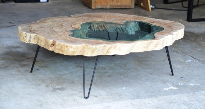 Журнальный столик из натурального дерева и стекла бирюзового оттенка.