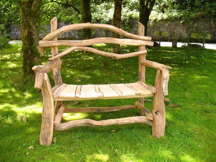 Деревянная скамейка из светлой породы древесины в саду.