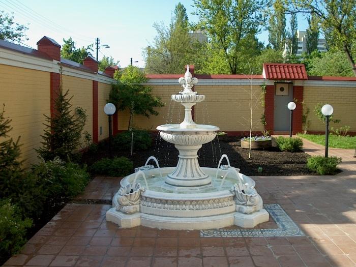 Белый керамический фонтан, который идеально впишется в любой садовый участок.