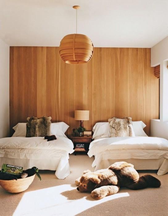Стена, полностью обшитая деревянной панелью из светлой породы дорогой древесины.