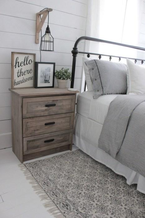 Состаренная деревянная тумбочка в светлом интерьере спальной комнаты.