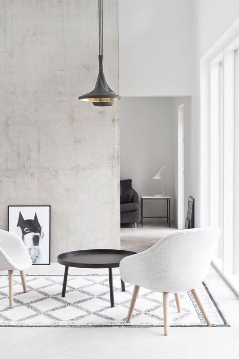 Традиционное для минималистского стиля сочетание черной и белой цветовой гаммы в интерьере гостиной комнаты.