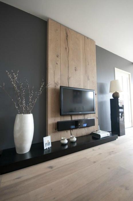 Зона для просмотра телевизора выделенная контрастной деревянной панелью, которая ярким пятном выделяется на фоне стены тёмного оттенка.