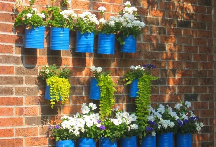 Вертикальное украшение стен растениями в горшках из жестяных банок.