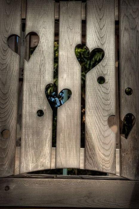 Украсить скучное деревянное ограждение можно, аккуратно вырезав в нем отверстия в виде сердечек.