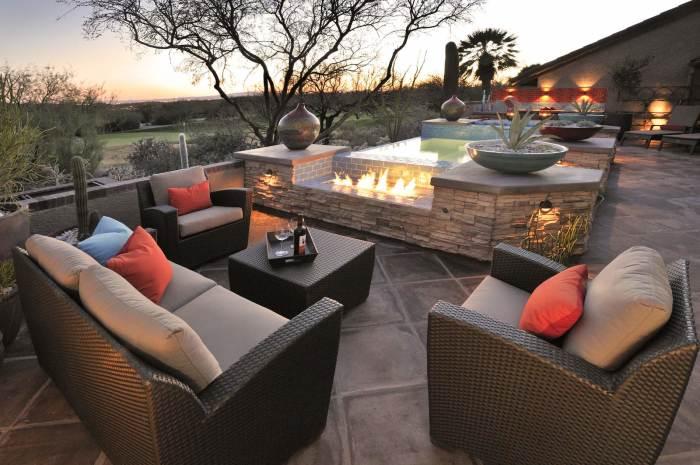 Стильная терраса с комфортабельной современной мебелью, местом для разведения огня и искусственным водоёмом.