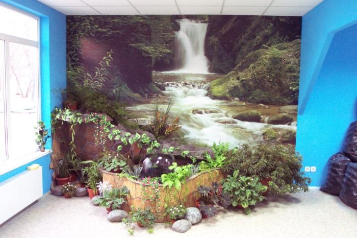 Небольшой декоративный сад на фоне картины водопада.