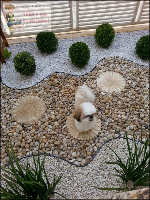 Чучело маленькой собаки на фоне ландшафтной композиции из гальки.