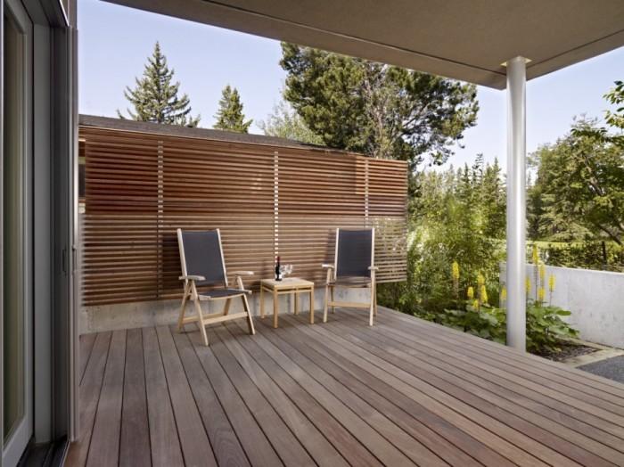 Открытая терраса с деревянной перегородкой может стать дополнительной комнатой на даче.