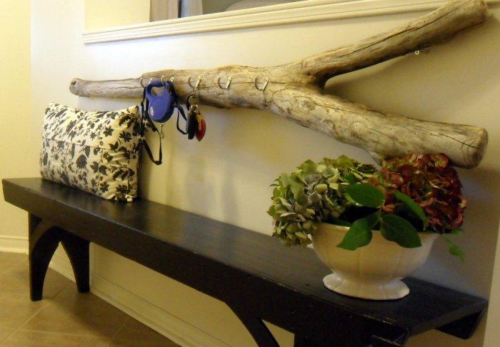Вешалка в прихожей, за основу которой взят большой деревянный спил.